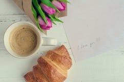 Koppen kaffe med gifflet, buketten av rosa tulpan och anmärkningar ÄLSKAR JAG DIG Arkivfoto