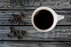 Koppen kaffe med kaffebönor beskådar överst träbakgrund royaltyfria bilder