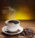 Koppen kaffe med kaffebönor near det. Royaltyfria Foton