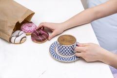 Koppen kaffe med mjölkar, donuts, kvinnors händer arkivfoto