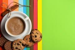 Koppen kaffe med mjölkar eller cappuccino med kakor och kanel på färgrik bakgrund Drink med koffein eller kakao arkivfoton
