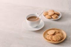 Koppen kaffe med mjölkar eller cappuccino med kakor på ljus stenbakgrund Drinken med koffein eller kakao med mjölkar söt kopp för arkivbilder