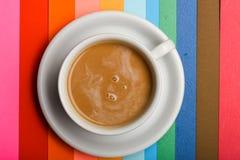 Koppen kaffe med mjölkar eller cappuccinodrycken på färgrikt som regnbågebakgrund Drinken med koffein eller kakao med mjölkar royaltyfri foto