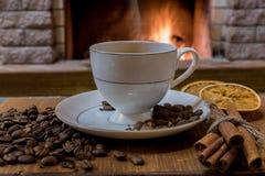 Koppen kaffe med mjölkar och kaffebönor runt om koppen, den kanderade frukten och de kanelbruna pinnarna för hemtrevlig spis royaltyfria bilder