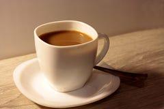 Koppen kaffe med mjölkar på en trätabell arkivfoto