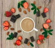 Koppen kaffe med mjölkar, choklad och jordgubbar på träbakgrund Lekmanna- lägenhet Royaltyfria Bilder