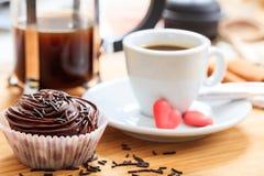 Koppen kaffe och en kopp bakar ihop på en träyttersida Arkivfoto