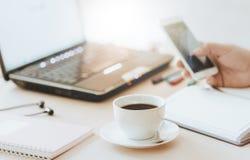 Koppen kaffe och ilar telefonen med handen av affärsmannen som använder bärbar datordatoren arkivfoto