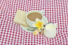 Koppen kaffe och koppen av mjölkar rött pålagt tyg, vit fotografering för bildbyråer