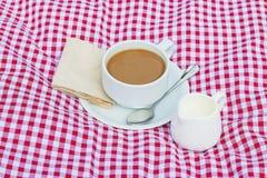 Koppen kaffe och koppen av mjölkar rött pålagt tyg, vit arkivbilder