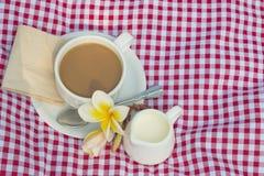 Koppen kaffe och koppen av mjölkar rött pålagt tyg, vit royaltyfri bild