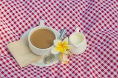 Koppen kaffe och koppen av mjölkar rött pålagt tyg, vit royaltyfri foto
