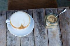 Koppen kaffe som kostar på en träliten tabell, en cappuccino, kaffe med, mjölkar, doftande en cappuccino arkivfoto