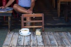 Koppen kaffe som kostar på en träliten tabell, en cappuccino, kaffe med, mjölkar, doftande en cappuccino royaltyfri bild