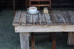 Koppen kaffe som kostar på en träliten tabell, en cappuccino, kaffe med, mjölkar, doftande en cappuccino arkivbilder