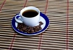 Koppen kaffe som omkring beströs med kaffekorn Arkivbild