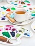 Koppen med te och kakan omgav vattenfärgpaletten Fotografering för Bildbyråer