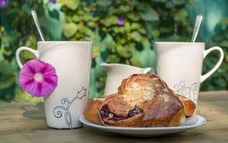 Koppen, melkkruik en een plaat op de lijst Vers broodje op een plaat Thee het drinken in het midden van een zonnige dag Stock Foto's