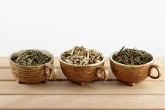 Koppen met groene en witte theebladen op een witte achtergrond Royalty-vrije Stock Foto