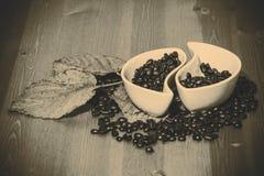 Koppen met koffiebonen op een houten lijst Royalty-vrije Stock Afbeeldingen