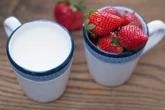 Koppen met verse stawberries en melk worden gevuld die Stock Afbeelding