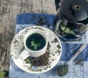 Koppen och vit för grönt te pläterar a-te som tillbringaren på sidan förläggas på en torkduk på en träbakgrund Royaltyfria Bilder