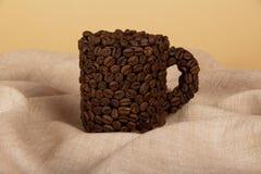 Koppen som fylls med kaffekorn royaltyfri foto