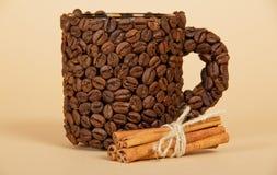 Koppen som göras från kaffekorn och kanel arkivfoto