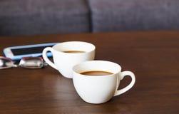 Koppen van hete koffie op houten lijst en glazen Royalty-vrije Stock Foto's