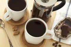 Koppen van koffie en chocolade op lijst Royalty-vrije Stock Afbeeldingen