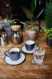 Koppen van koffie en glas water op koffielijst Stock Foto's