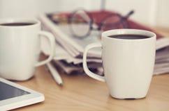 Koppen van koffie en krant op lijst Stock Foto's