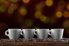 Koppen van koffie met koffiebonen op gouden achtergrond, productfotografie voor koffiewinkel Stock Afbeelding