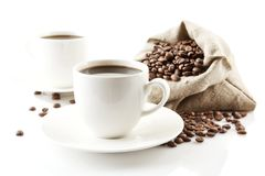 Koppen van koffie met schotel met zak met koffiebonen op wit Royalty-vrije Stock Afbeeldingen