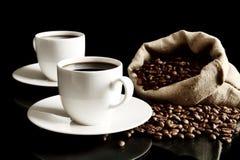 Koppen van koffie met schotel met zak met koffiebonen op zwarte Royalty-vrije Stock Afbeelding