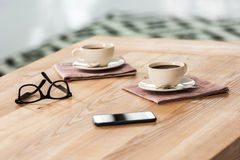 Koppen van koffie, oogglazen en smartphone op lijst in koffie Stock Afbeeldingen