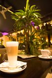 2 koppen van koffie op de lijst in romantische koffie met palm en lichten, latte en espresso Stock Afbeelding