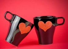 Koppen van melk met decoratief hart op rode achtergrond, concept valentijnskaartdag Stock Foto
