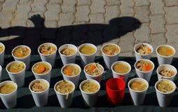 Koppen van soep bij een soepkeuken voor de armen stock foto's