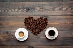 Koppen van vers gebrouwen koffie met een volle smaak en melkachtige dichtbij bonen in hartvorm op de donkere houten mening van de Royalty-vrije Stock Foto's