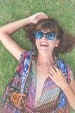 koppla av för gräs Bästa sikt av den härliga unga kvinnan i solglasögon och pareoen som ligger på det gröna gräset i parkera av Royaltyfri Fotografi