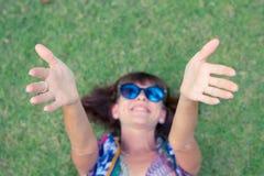 koppla av för gräs Bästa sikt av den härliga unga kvinnan i solglasögon och pareoen som ligger på det gröna gräset i parkera av Royaltyfri Foto