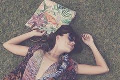 koppla av för gräs Den bästa sikten av den härliga unga kvinnan i solglasögon och pareoen som ligger på det gröna gräset med stra Arkivfoto