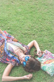 koppla av för gräs Den bästa sikten av den härliga unga kvinnan i solglasögon och pareoen som ligger på det gröna gräset med stra Fotografering för Bildbyråer
