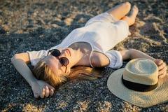 Koppla av för sommarkvinna som ligger i sanden på stranden royaltyfri bild