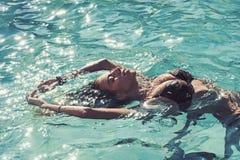 Koppla av i brunnsortsimbass?ng, uppfriskning och skincare Sommarsemester och lopp till havet Sexig kvinna p? det karibiska havet royaltyfri bild