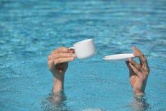 Koppla av i vatten - händer över - bevattnar innehavkoppen och den lilla plattan Arkivfoto