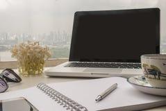 Koppla av kontorsutrymme för arbete på en vit tabell vid balkongen royaltyfri fotografi