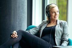 Koppla av lyssna för kvinna till musik Arkivbilder