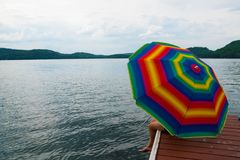Koppla av med detfärgade parasollparaplyet på en lakesideskeppsdocka arkivfoton